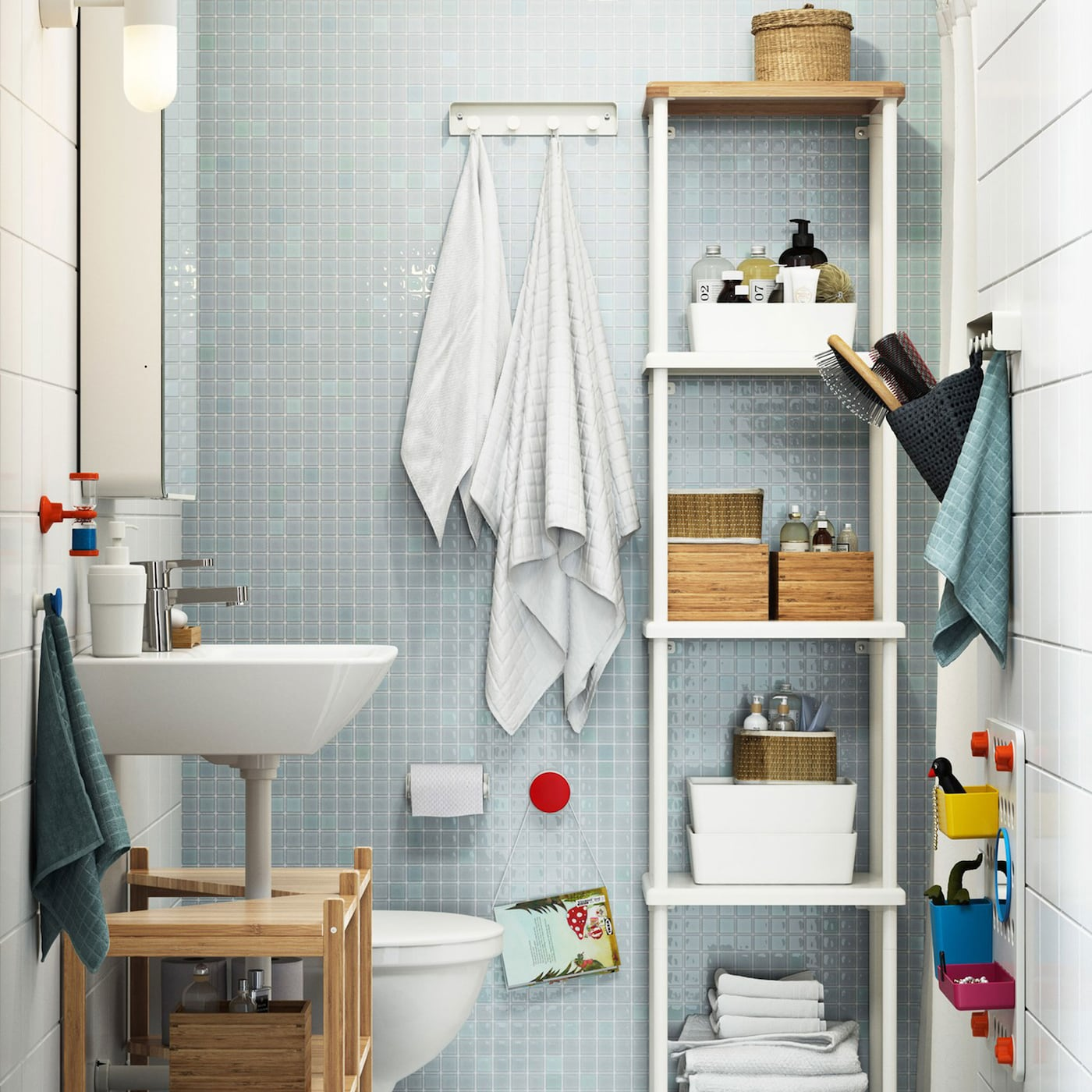 Small family bathroom with white and light blue tiles, and DYNAN tall white open shelving unit filled with bathroom accessories.