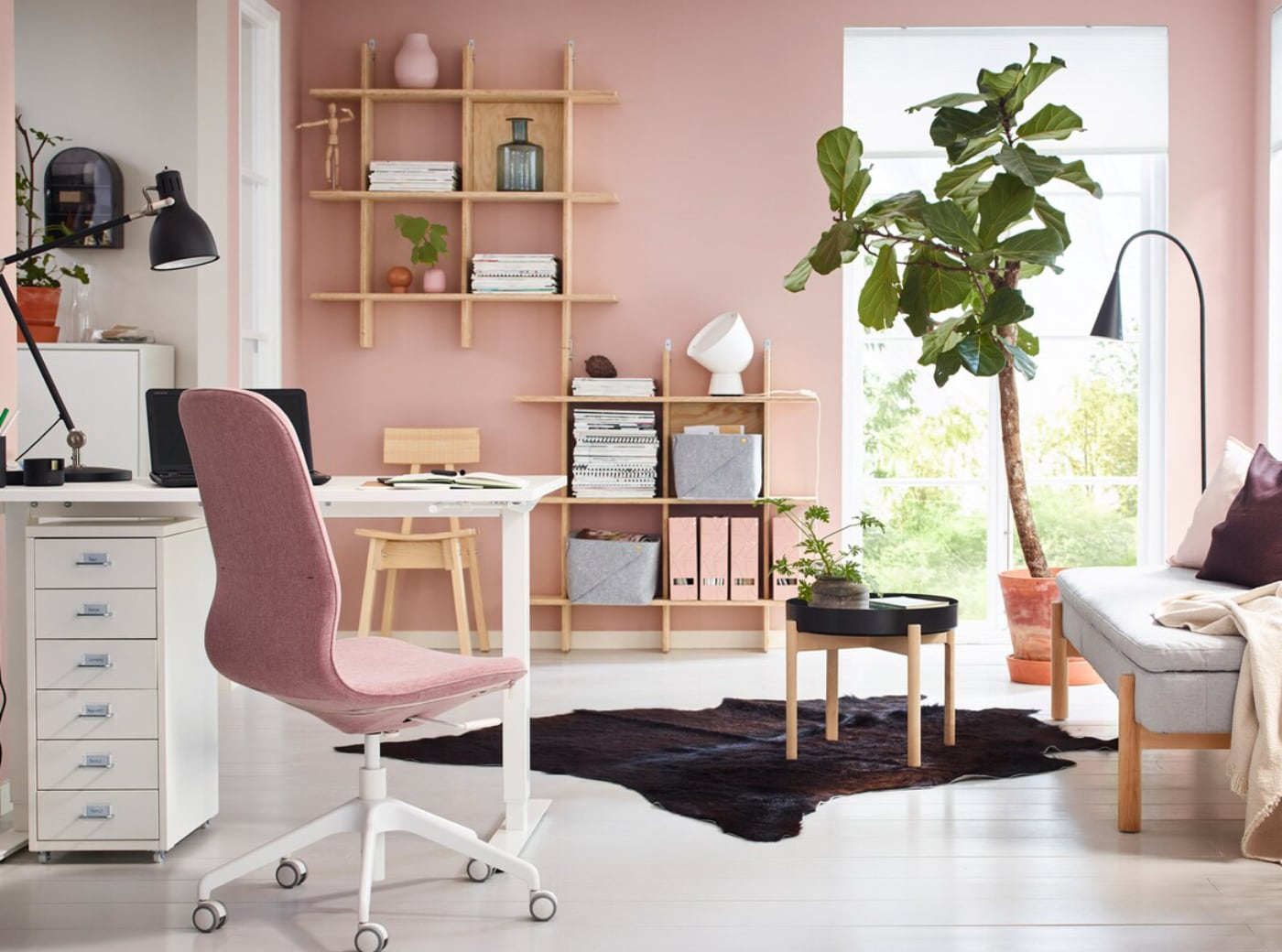 Small home office, with a LINNMON/KRILLE table in white with legs on castors, some shelves, storage cabinets and a sofa bed.