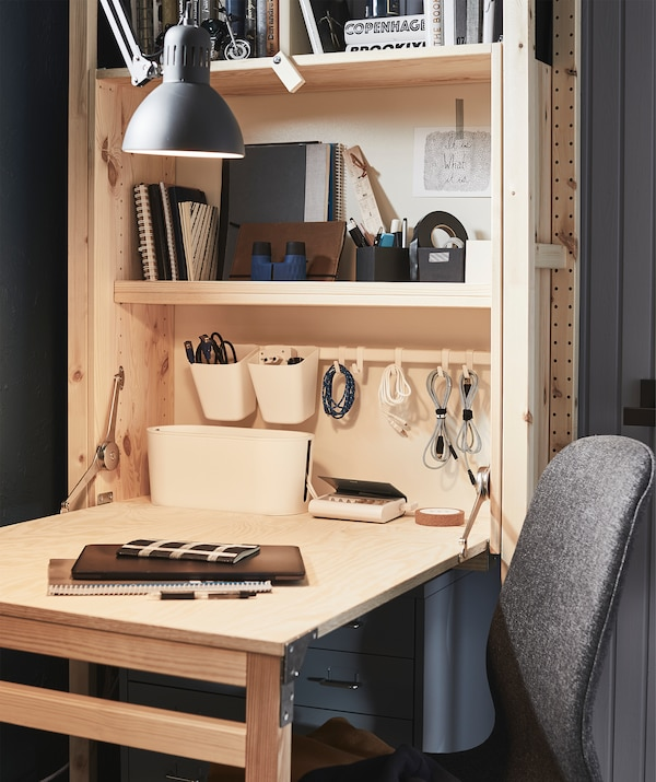 Small home workspace formed by storage unit with folded-out desk surface. Cables and office stuff on the shelves.