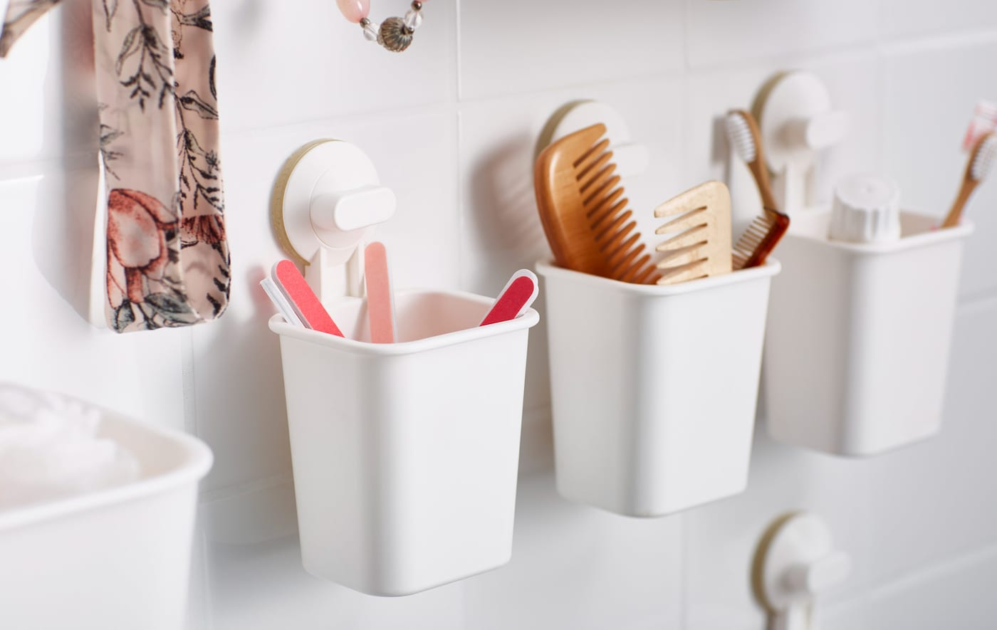 Small plastic baskets, attached to the bathroom wall with suction cups, and holding toiletries and accessories.