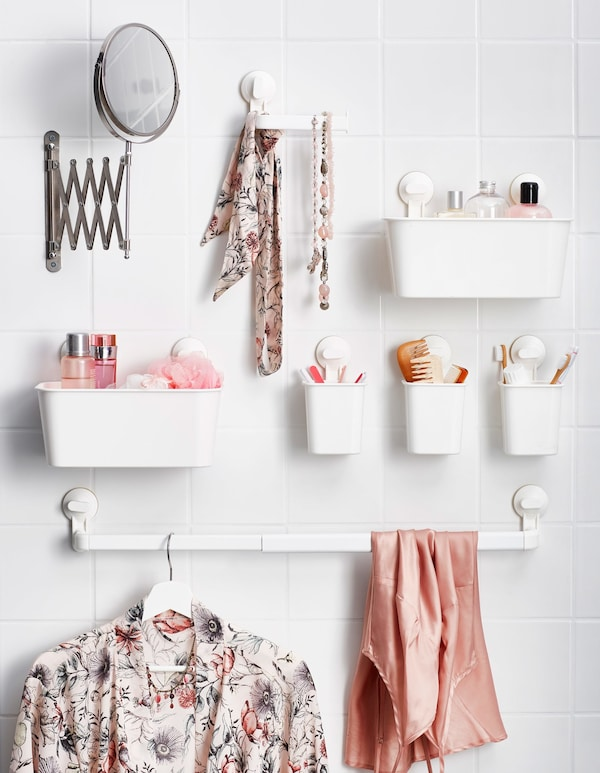 Small plastic baskets attached to the bathroom wall with suction cups, holding toiletries and accessories.
