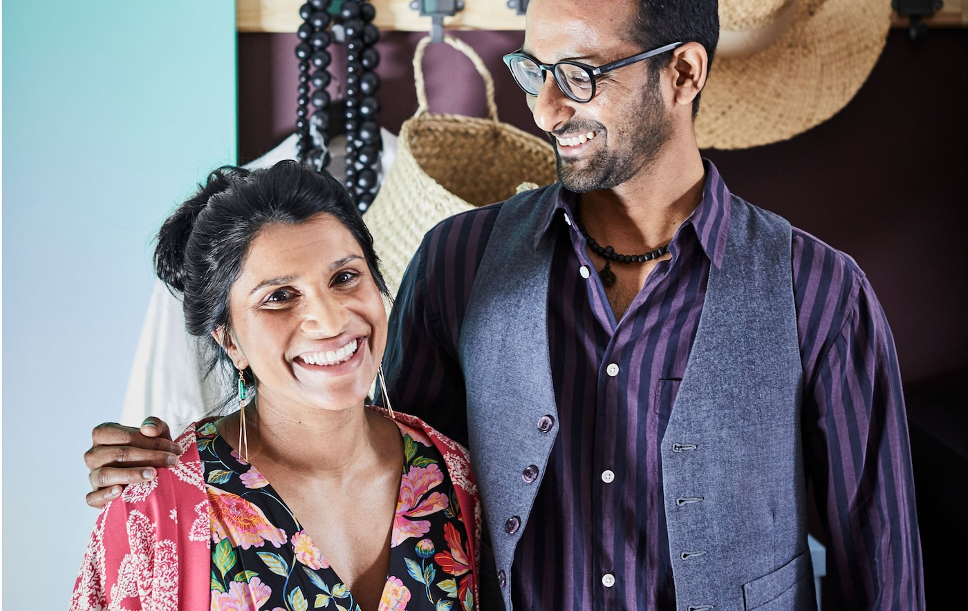 Smiling, thirty-something woman and man standing affectionately together; clothing and accessories on a rack behind them.