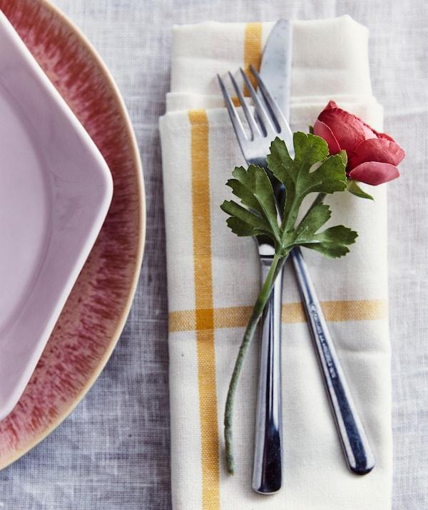SMYCKA Kunstblume Ranunkel auf IKEA 365+ Besteck, das auf einer Serviette platziert wurde. Daneben ist ein rosafarbener Teller zu sehen.