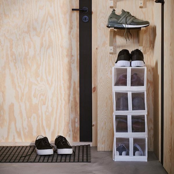 صناديق أحذية ضيّقة بيضاء مكدسة على حائط ضيق بجوار الباب. وفوق الصناديق توجد حاملات عليها المزيد من الأحذية.