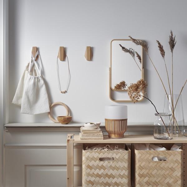 صناديق تخزين من الخيزران في وحدة خشبية، ومرآة وخطافات خشبية على جدار أبيض.