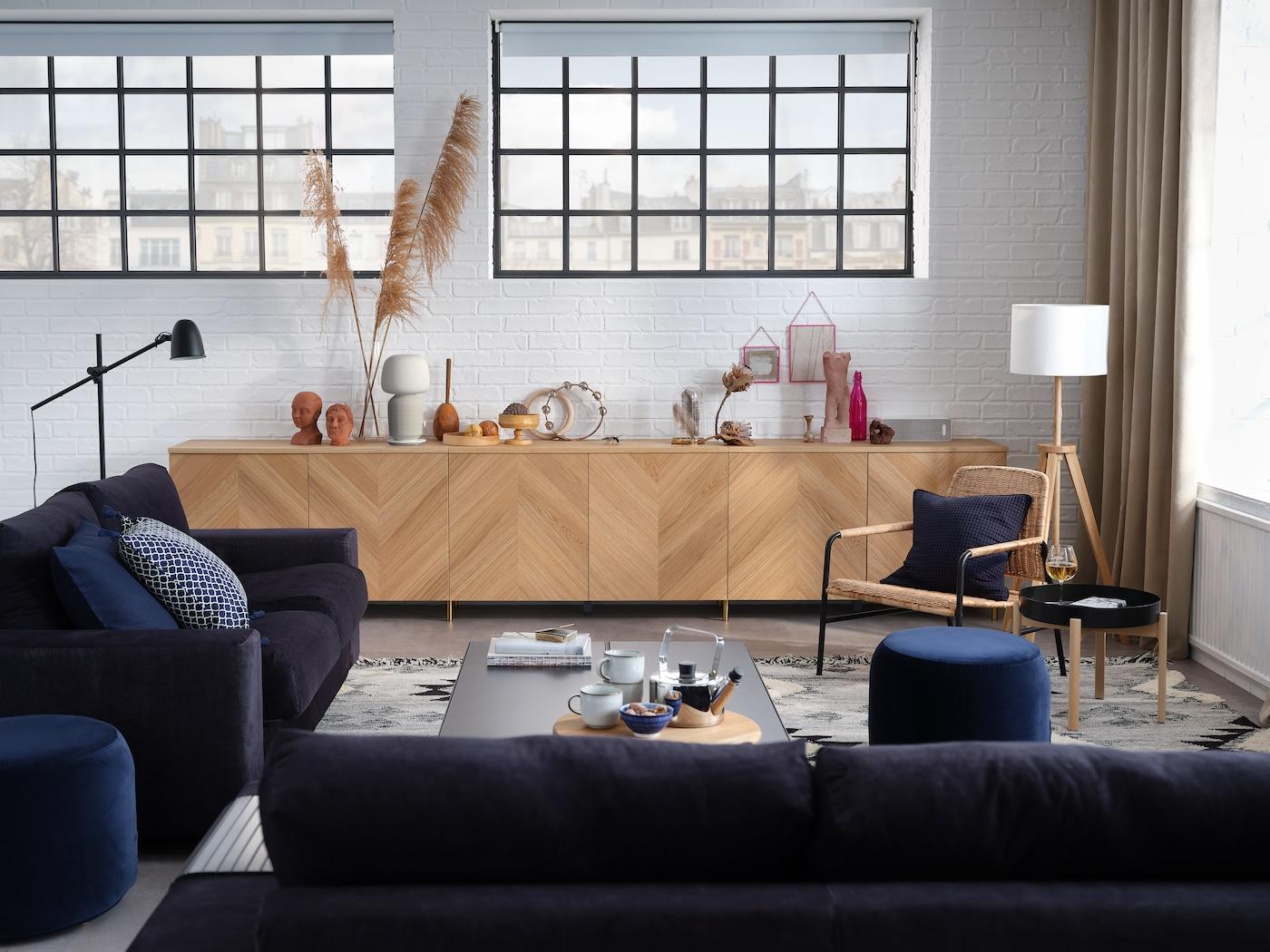 Snyggt vardagsrum med 3-sitssoffa, 2-sitsbäddsoffa, förvaringskombination med dörrar och en fåtölj.