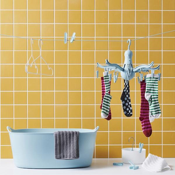 Socken an einer PRESSA Miniwäschespinne in Türkis, die zusammen mit Wäscheklammern und Kleiderbügeln an einer Leine vor einer gelb gefliesten Wand und über einem blauen Wäschekorb hängt.