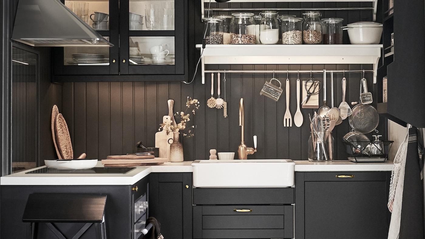 Sötét, hangulatos konyha, fekete szekrényekkel és fiókokkal, fekete fa falakkal, fehér polcokkal és munkalapokkal.
