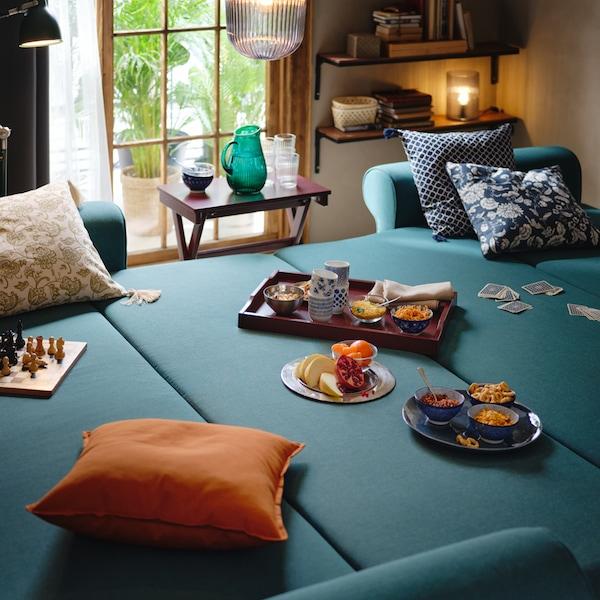 Sötét türkizkék VRETSTORP kinyitható kanapé felnyitott állapotban a nappaliban, rajta párnák, játékok és több tálca harapnivaló.