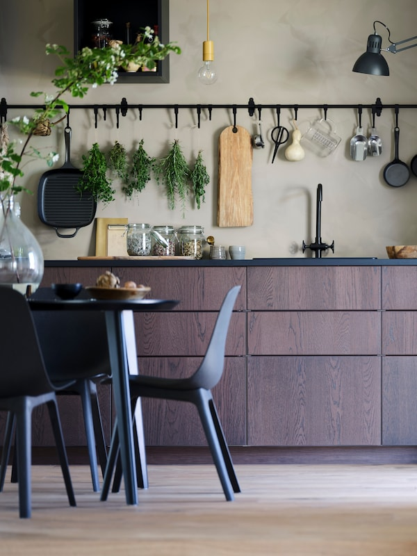 Sötétbarna konyha fekete munkalappal és fekete mosogatóval. A bézs falon fekete HULTARP függő tárolórendszer van. Az előtérben egy fekete asztal és fekete-kék BALTSAR székek vannak.