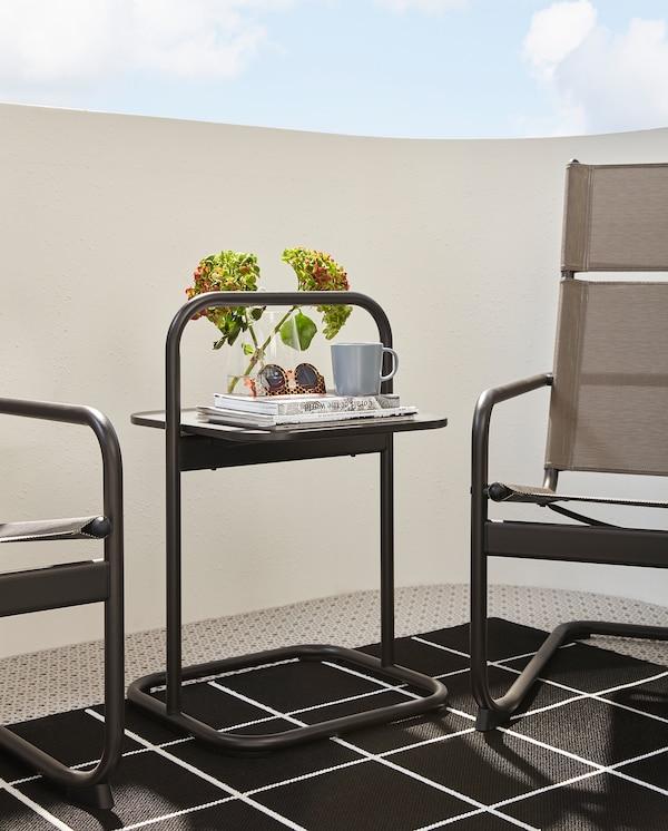 Sötétszürke HUSARÖ kisasztal, fogantyúkkal, egy szőnyegen, két fotel között.