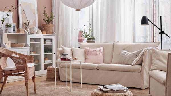 Sofa 3 tempat duduk, ambal tenunan rata, kerusi berlengan rotan dengan kusyen, kabinet berpintu kaca dan kabinet 2 pintu.