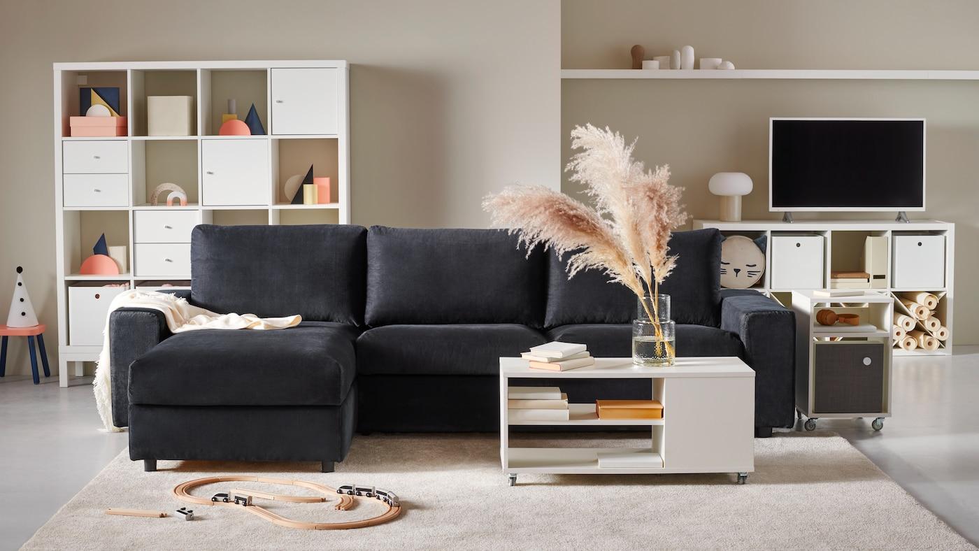 Sofá azul marino VIMLE en un living con tonos claros o pasteles, como el blanco y rosado pálido. Atrás de el hay muebles blancos llenos de decoración, libros y un televisor con una lámpara gris con blanco.