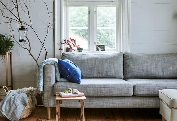 Sofa berwarna kelabu di hadapan tingkap, alas bulu biri-biri disimpan di dalam bakul di sebelahnya dan dahan pokok dipamerkan di dalam vas kaca yang besar.