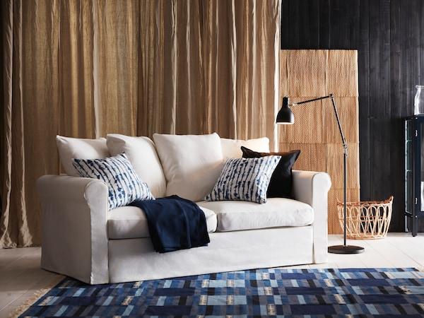 Sofá blancho sobre alfombra con trama en tonos azules y fondo beige.