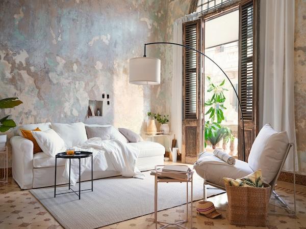 Sofá blanco pegado a una pared en beige y gris con varios cojines, una mesa auxiliar negra y una silla auxiliar blanca.