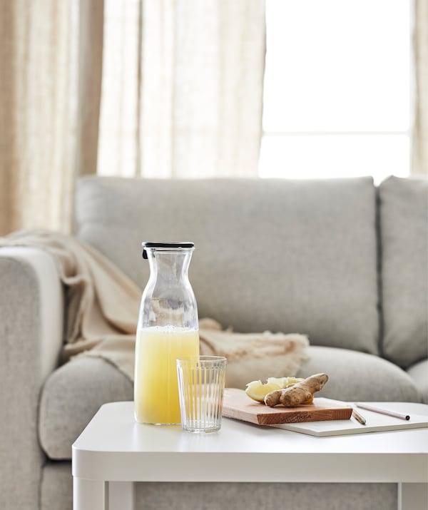 Sofá com a mesa de apoio TINGBY à frente, sobre a qual está uma garrafa de mesa com um sumo de fruta e uma tábua de cortar com pedaços de gengibre e limão.