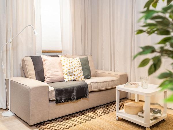 Sofá de dois lugares KIVIK em bege por cima de um tapete e com uma mesa de centro branca com rodas