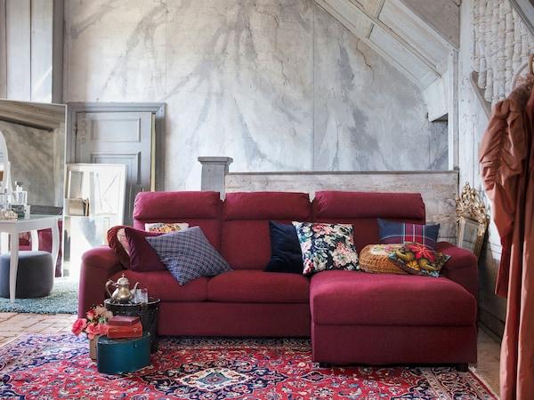 Sofá de tres prazas LIDHULT vermello-marrón con chaiselongue e moitos coxíns nun cuarto espazoso sobre unha alfombra vermella oriental.
