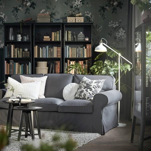Sofa EKTORP z szarym pokryciem stojąca w pokuju z kwiecistą tapetą.
