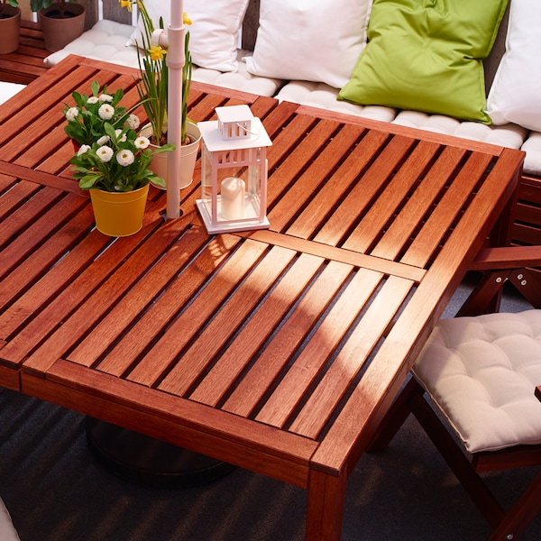 Sofá em branco com almofadas e mesa para exterior quadrada feita em madeira de acácia castanha com decorações em cima.