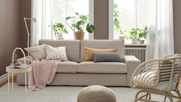 Sofa KIVIK z beżowym pokryciem staojąca w jasnym pokoju dziennym z brązowymi ścianami.