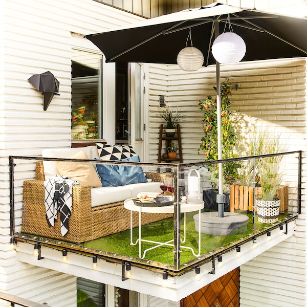 Sofa luar dua tempat duduk moden SOLLERÖN yang berwarna coklat/kuning air di balkoni kecil dengan meja rendah dan payung.