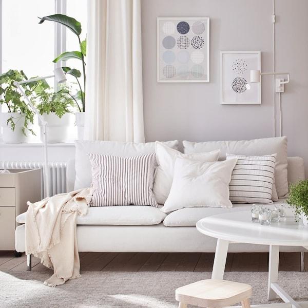 Sofa modułowa SÖDERHAMN z plduszkami dekoracyjnymi w jasnoszarym pokoju dziennym.