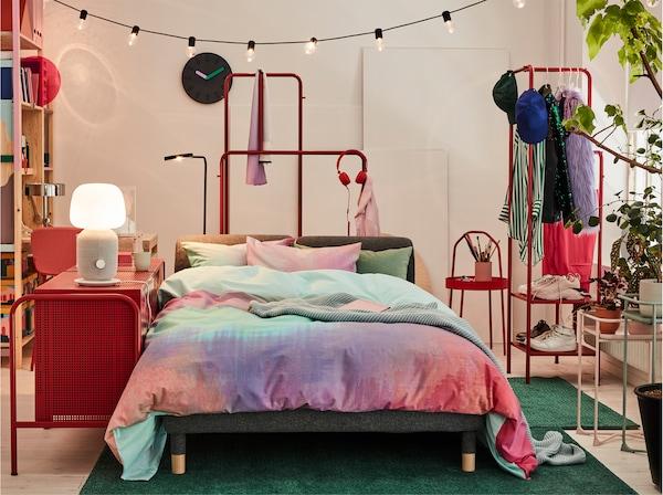 Sofa od koje dobijaš krevet, pokrivena šarenim krevetnim tekstilima, uz komodu koja služi kao noćni stočić.