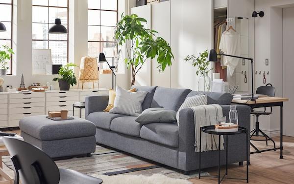 Sofá VIMLE gris oscuro en un living con luz de día. Hay mesas de living negras y muebles blancos como estantería.