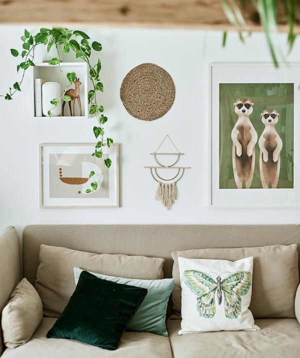 Sofa visokog naslona sa zelenim ukrasnim jastucima ispred bijelog zida s uokvirenom ilustracijama, zidnim ukrasima i biljkama.