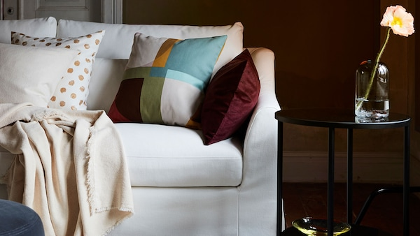 sofa with STENMÄTARE cushion with mix of other cushion and  throws.