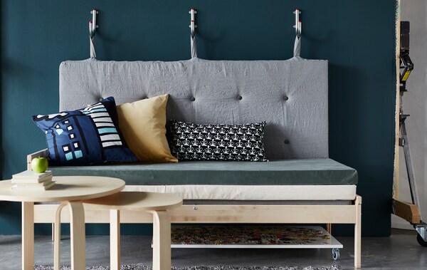 Sofa zrobiona z materacy, z oparciem wiszącym na hakach na ścianie