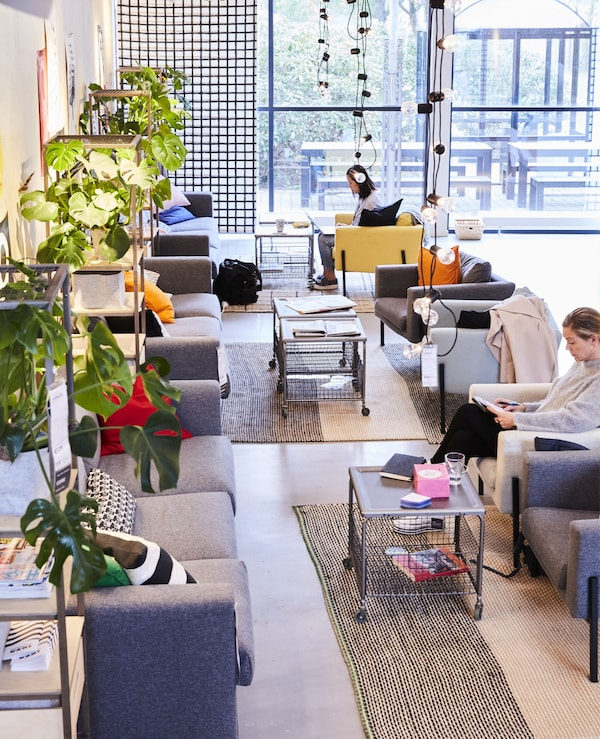 Sofas, armchairs and coffee tables in an open-plan workspace.