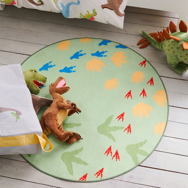 Soft toy dinosaurs lying on the JÄTTELIK rug featuring a pattern of dinosaur footprints placed in a children's bedroom.