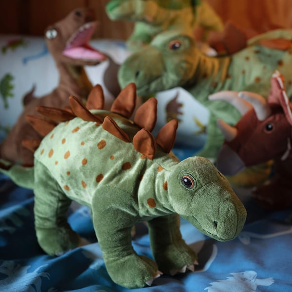 Soft toy dinosaurs on a blue blanket