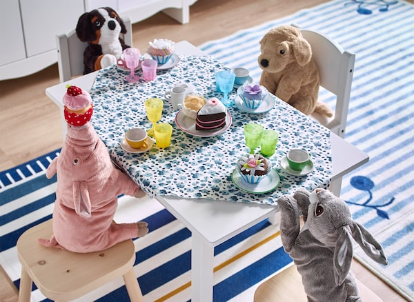 Soft toys sitting around a small table with a tea party set-up.