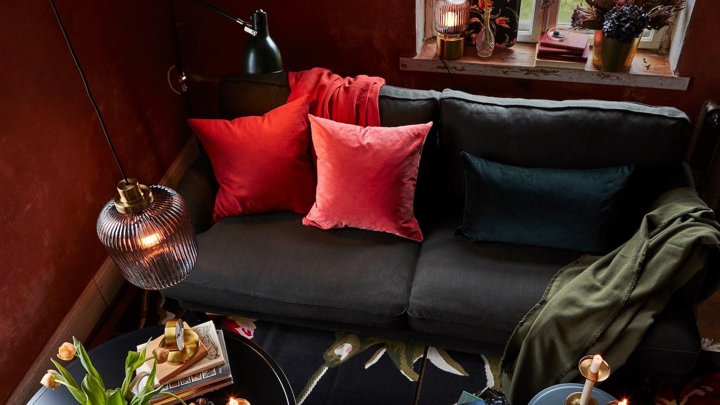 Soggiorno caldo e accogliente, con lampade a sospensione, da terra e da tavolo, e un divano con cuscini colorati.