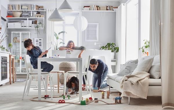 Soggiorno compatto con letto, divano, tavolo, piccola cucina e mobili, e una famiglia che gioca con un trenino LILLABO.