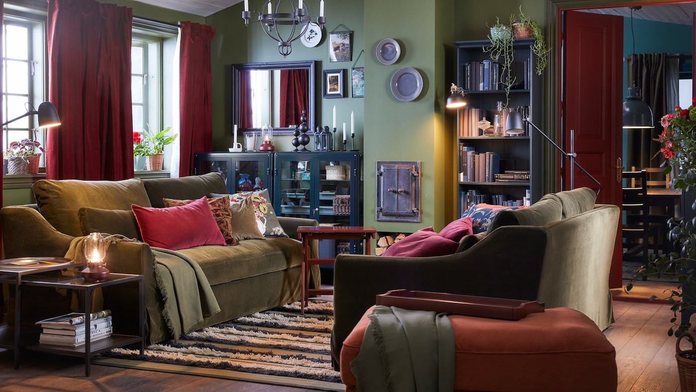 Soggiorno con due divani con cuscini e plaid, lampadario, vetrine, scaffale e specchio.