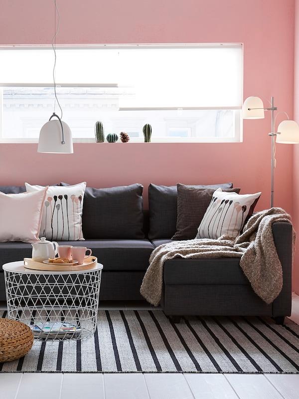 Soggiorno con pareti rosa e pavimento bianco. Sotto una grande finestra rettangolare c'è un divano angolare, grigio scuro. Davanti al divano un tavolino con contenitore e un pouf in rattan, entrambi sopra un tappeto grigio chiaro con delle strisce blu scuro.