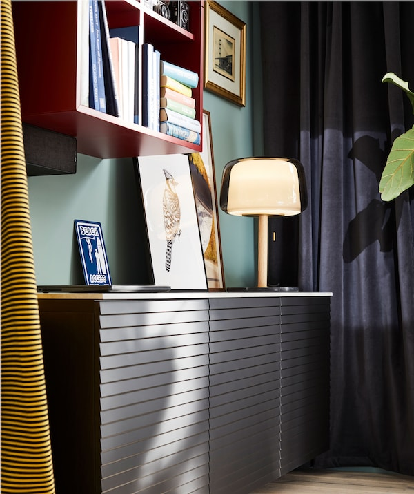 Soggiorno con un mobile con ante basso e fissato a parete, una libreria, tende, una lampada e altre decorazioni dai colori intensi - IKEA