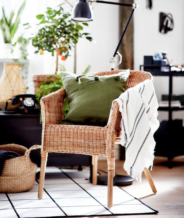 Soggiorno dallo stile grafico in bianco e nero, con elementi in materiali naturali e una poltrona AGEN in rattan con cuscino verde.