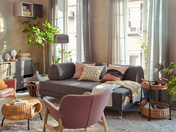 Soggiorno tornato alla normalità dopo essersi trasformato in camera degli ospiti, con un divano letto FLOTTEBO, piante, tessili e un grande tappeto - IKEA