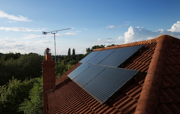 Solar panels mounted on top of the roof of a residential home, with clear bright skies.