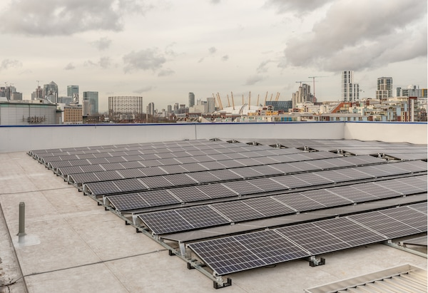 Solar panels on a roof with a city skyline behind.