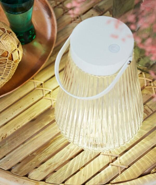Solárna stojacia lampa SOLVINDEN s jemným svetlom vedľa podnosu na stole vyrobená z tenkých drevených latiek.
