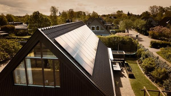 Solcellspaneler på ett svart tak på en villa i ett villakvarter.