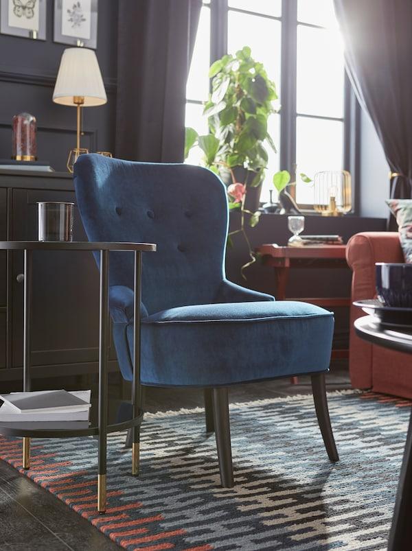 Solfyldt stue med mørke vægge, hvor en blå REMSTA lænestol er placeret i et hjørne af et farvestrålende, mønstret RESENSTAD tæppe.