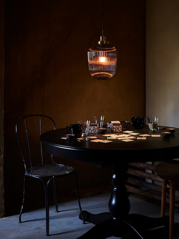SOLKLINT pendant lamp made in grey glass lighting up a dark room, hanging above a round black table with a card game.